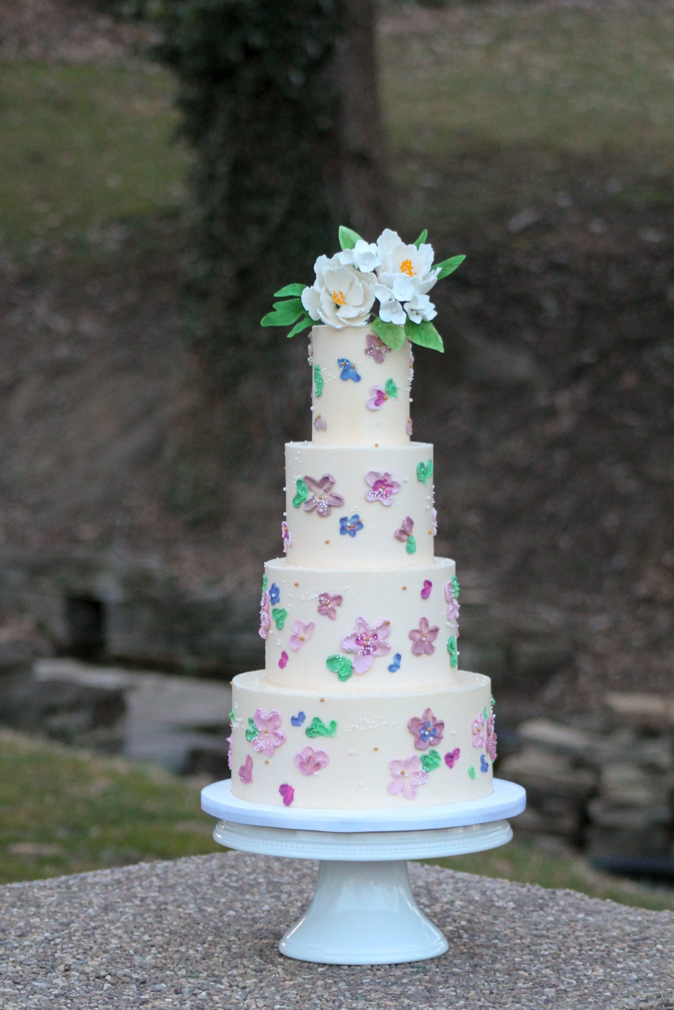 Tiered-painted-buttercream-floral-wedding-cake-with-white-sugar-flowers-from-Four-Oaks-Bakery-in-Pittsburgh-PA